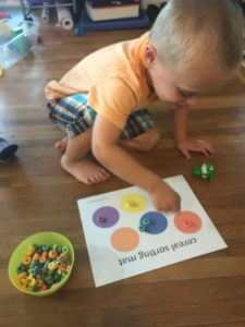 child sorting colored cereal