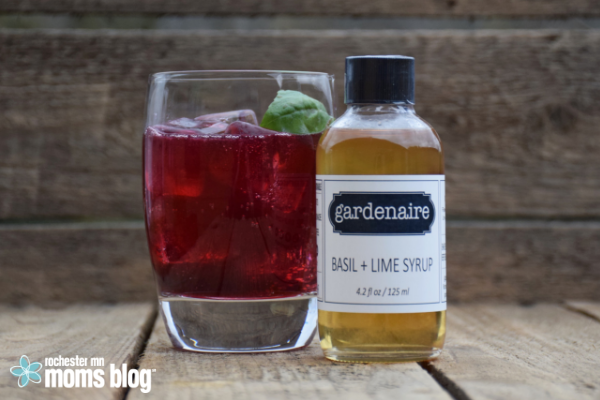 a glass filled with a summer sparking beverage and bottle of flavored syrup from Gardenaire