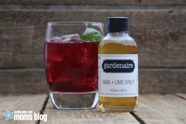 a glass filled with a red summer sparking beverage and bottle of flavored syrup from Gardenaire