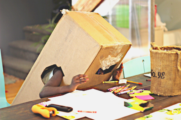 child playing with cardboard box and craft supplies
