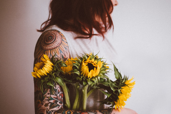 woman with shoulder tattoo holding flowers
