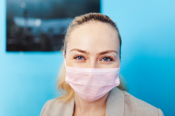 woman smiling under mask